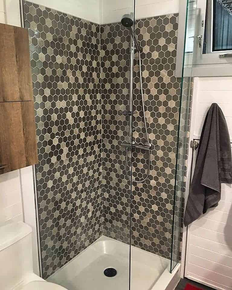 With A Flush Toilet And A Geometrically Tiled Glass Walled Shower Stall,  The Bathroom Looks Quite Comfortable.
